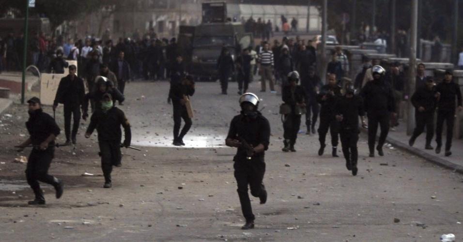 7.mar.2013 - Policiais correm em direção a manifestantes opositores ao presidente egípcio Mohamed Mursi, na praça Tahrir, no Cairo (Egito), nesta quinta-feira (7), após suspensão das eleições no Egito