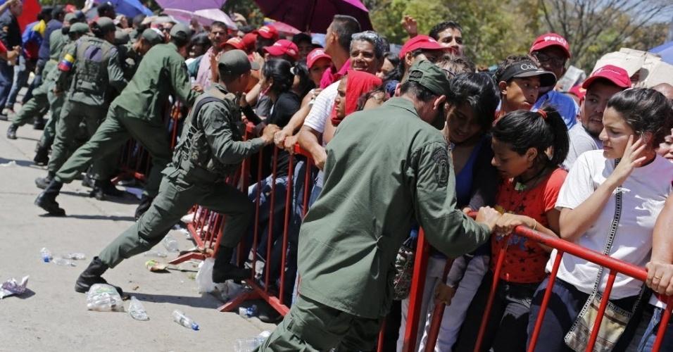 7.mar.2013 - Policiais tentam conter multidão que aguarda para ver o corpo do presidente da Venezuela, Hugo Chávez, que está sendo velado na Academia Militar, em Caracas, nesta quinta-feira (7). A espera na fila dura cerca de 12 horas, e muitos venezuelanos passaram mal com o calor que faz na capital do país