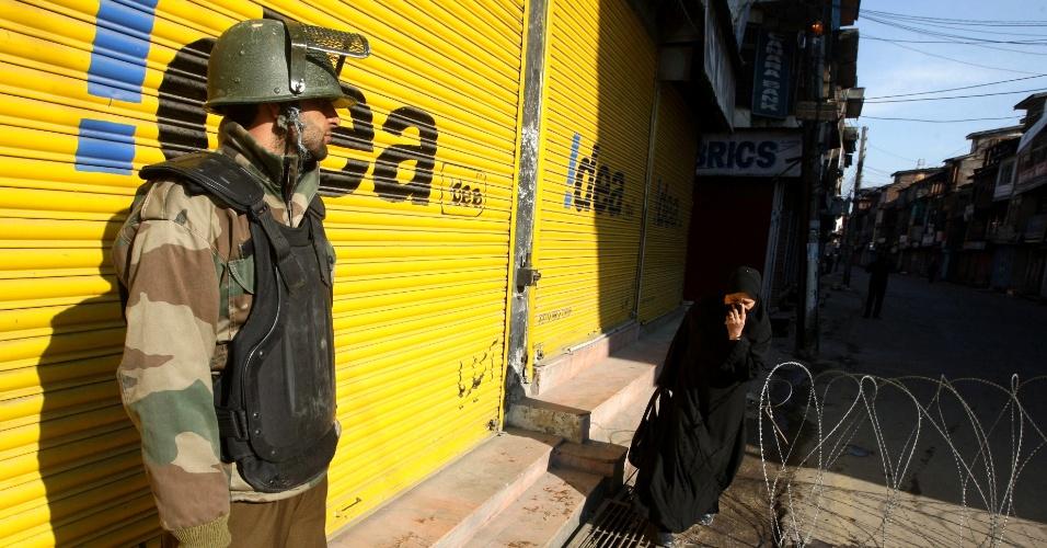7.mar.2013 - Policial indiano observa mulher muçulmana caminhar por cerca de arame farpada em rua de Srinagar, cidade onde foi imposto toque de recolher, após a escalada da violência na capital da Caxemira indiana e em toda região, depois que um soldado paquistanes foi morto, supostamente por soldados indianos