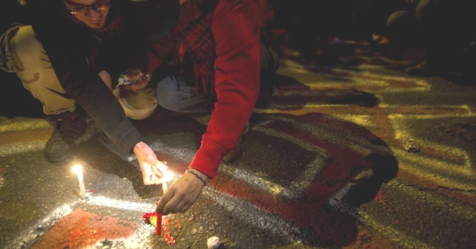 7.mar.2013 - Público acende velas e faz desenhos no chão, do lado de fora da embaixada da Venezuela em Bogotá, capital da Colômbia, na quarta-feira (6), para homenagear Hugo Chávez. O presidente da Venezuela morreu na terça-feira (5), aos 58 anos, vítima de um câncer na região pélvica