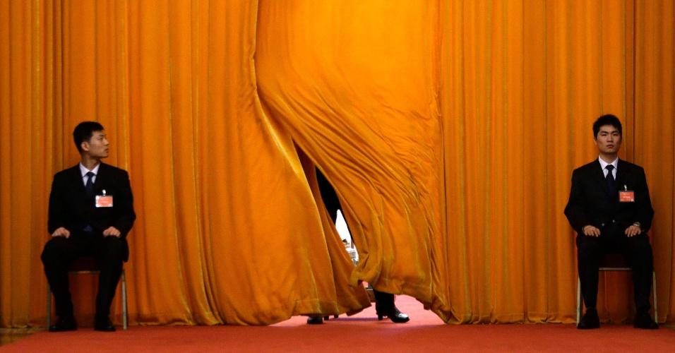7.mar.2013 - Seguranças guardam passagem no Grande Salão do Povo, em Pequim, local que recebe o 12º Congresso Nacional do Povo, que dura até o dia 17 de março. Segundo um oficial, a urbanização planejada, bancada pelo governo, ira sustentar os altos índices de crescimento do país pelos próximos anos
