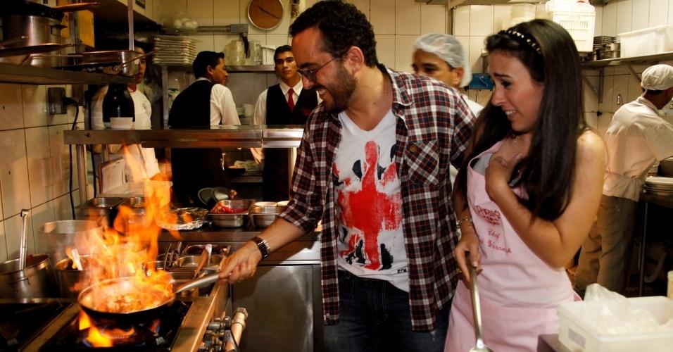 7.mar.2013 - A atriz Tatá Werneck, que está no elenco da próxima novela das nove da Globo, ajuda a preparar prato que terá seu nome junto do proprietário do estabelecimento, Isaac Azar