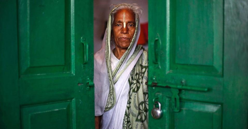 """8.mar.2013 - Viúva indiana posa às portas do 'ashram' (abrigo) de Meera Sahavagini, na cidade de Vrindavan, a 160 km de Nova Déli. Centenas de viúvas abandonadas por suas famílias vivem no abrigo. Segundo a tradição no país, quando seu marido morre, uma mulher deve renunciar a todos os """"prazeres mundanos"""", como usar roupas coloridas ou parecer atrativa, além de sofrer preconceito"""