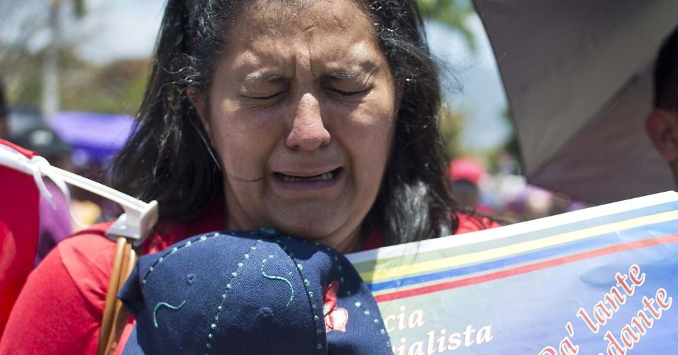 8.mar.2013 - Mulher chora do lado de fora do funeral de Hugo Chávez, em Caracas, nesta sexta-feira (8). O presidente venezuelano será transferido para um quartel onde será embalsamado