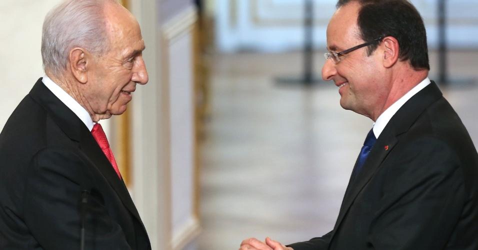 8.mar.2013 - O presidente francês, François Hollande (à dir.) aperta a mão de seu colega israelense, Shimon Peres, durante uma conferência de imprensa no palácio Elysee presidencial nesta sexta-feira (8) em Paris