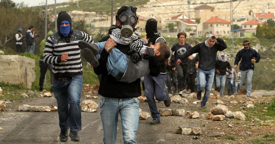 8.mar.2013 - Um manifestante palestino corre com um menino em seus braços durante confrontos com as forças de segurança israelenses após um protesto contra a desapropriação de terras palestinas por Israel nesta sexta-feira na aldeia de Kafr Qaddum, perto da Cisjordânia