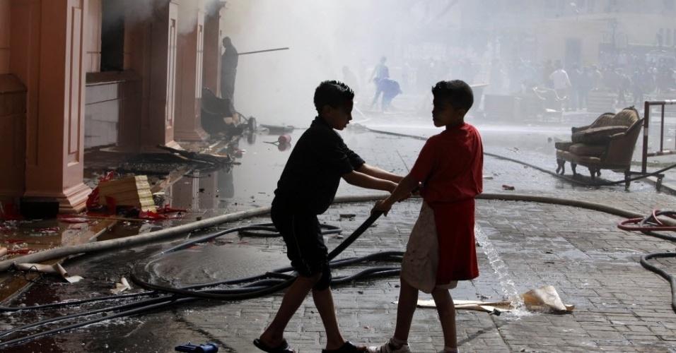 09.mar.2013 - Delegacia é incendiada por torcedores do Al Ahly e crianças ajudam a combater o fogo em protesto