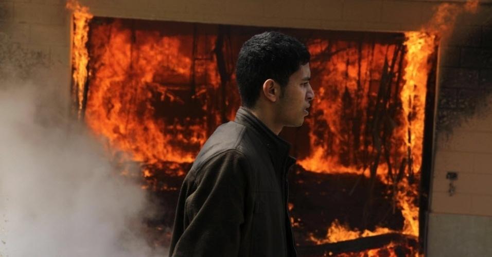 09.mar.2013 - Homem passa em frente a uma delegacia de polícia incendiada durante protestos da torcida do Al Ahly contra a condenação à morte de 21 pessoas em razão de batalha campal no Egito