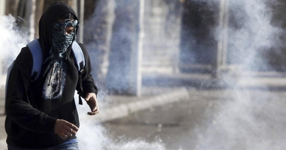 09.mar.2013 - Manifestante, que se opõe ao presidente Mohamed Mursi, corre do gás lacrimogêneo lançado pela polícia na ponte Qasr Al Nil, em Cairo, no Egito; parte da população se revoltou com a sentença que decretou pena de morte para 21 torcedores que estiveram envolvidos na batalha campal do ano passado