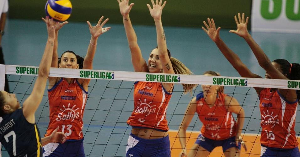 09.mar.2013 - Sheilla (e) e Thaisa, do Sollys/Nestlé, tentam bloquear ataque do Vôlei Amil pela primeira partida da semifinal da Superliga feminina; o Sollys venceu por 3 a 1