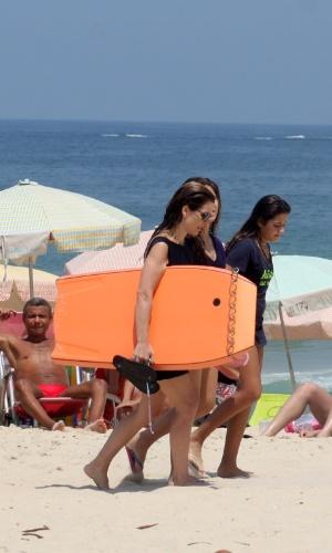 9.mar.2013 - Acompanhada das filhas, Cláudia Abreu aproveita o calor para praticar bodyboard em praia do Leblon, no Rio