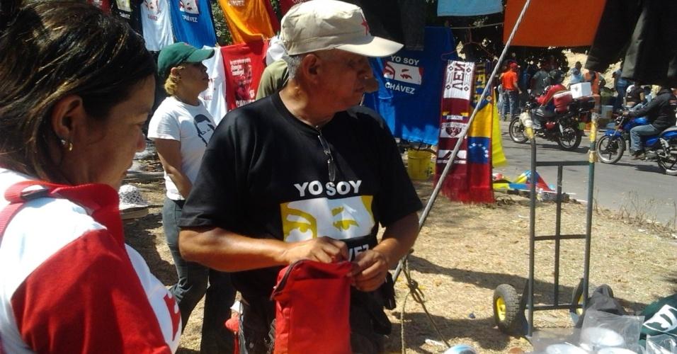 """9.mar.2013 - O vendedor Armando Osuna, 61, que diz que """"as camisetas em homenagem a Hugo Chávez estão vendendo como arroz"""", em rua que leva à Academia Militar, onde o corpo presidente está sendo velado, em Caracas, na Venezuela"""