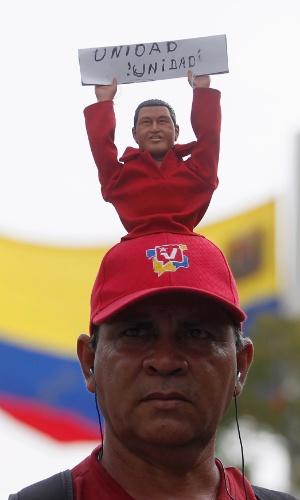 10.mar.13 - Homem vestido boné com boneco do líder Hugo Chávez espera do lado de fora da Academia Militar de Caracas, onde acontece o funeral do venezuelano