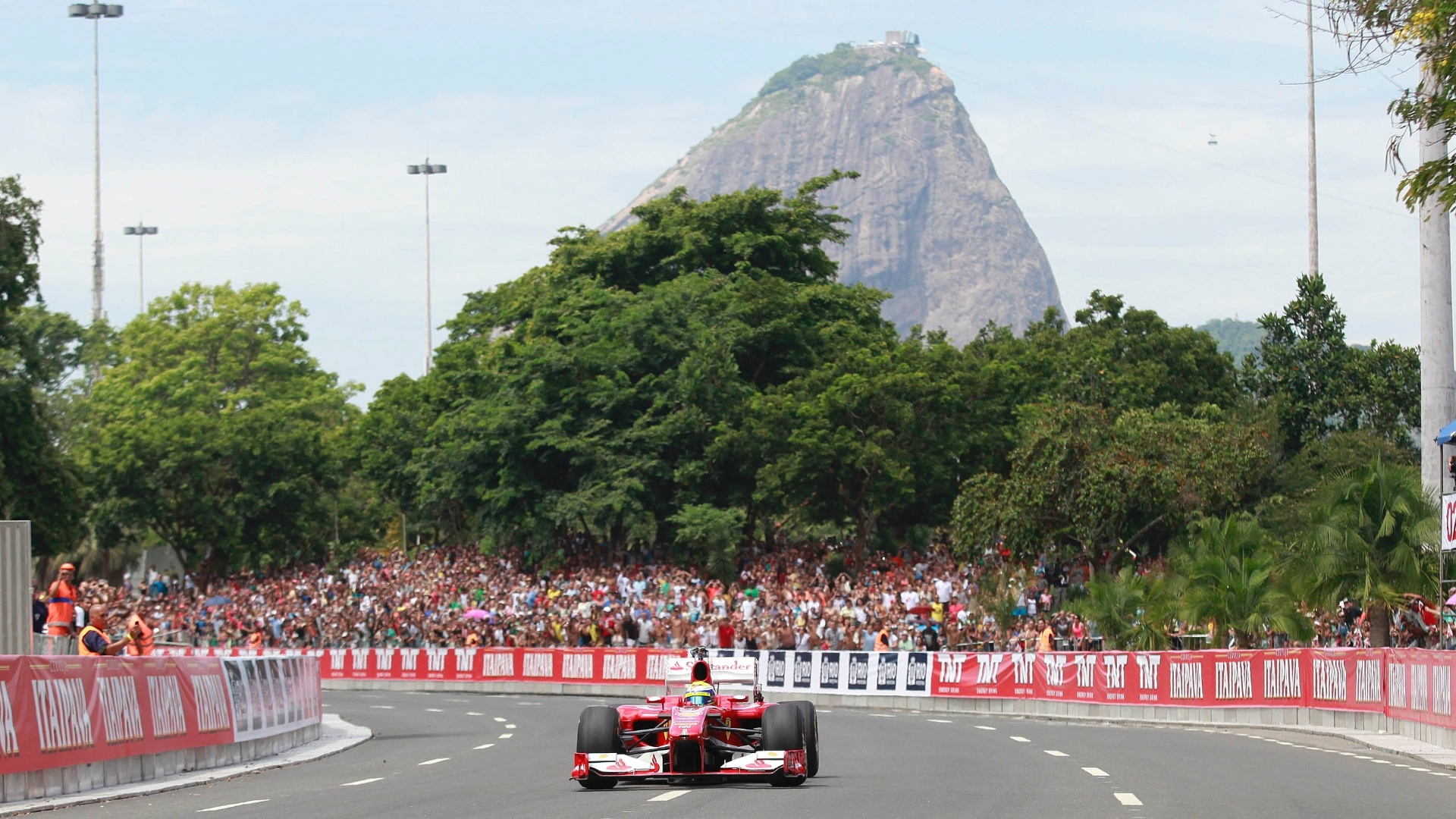 10.mar.2013 - A Ferrari de Felipe Massa é conduzida pelo piloto pelas ruas do rio de Janeiro, que ficaram tomadas pela presença do público