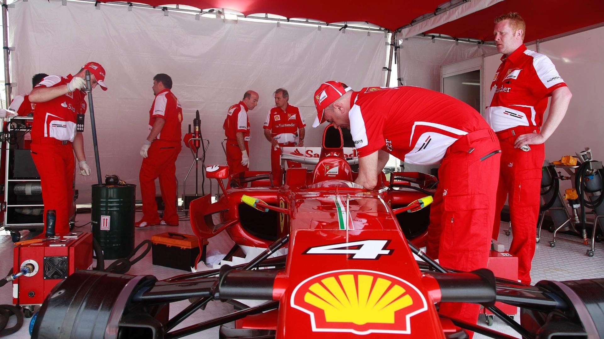 10.mar.2013 - Mecânico da Ferrari realiza últimos ajustes no carro n° 4, o de Felipe Massa, antes do brasileiro guiá-la pelas ruas do Rio