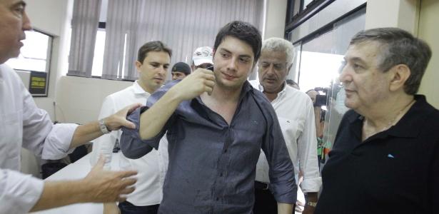 Alex Siwek (no centro) chega à delegacia, no dia do acidente que mutilou o braço de um ciclista