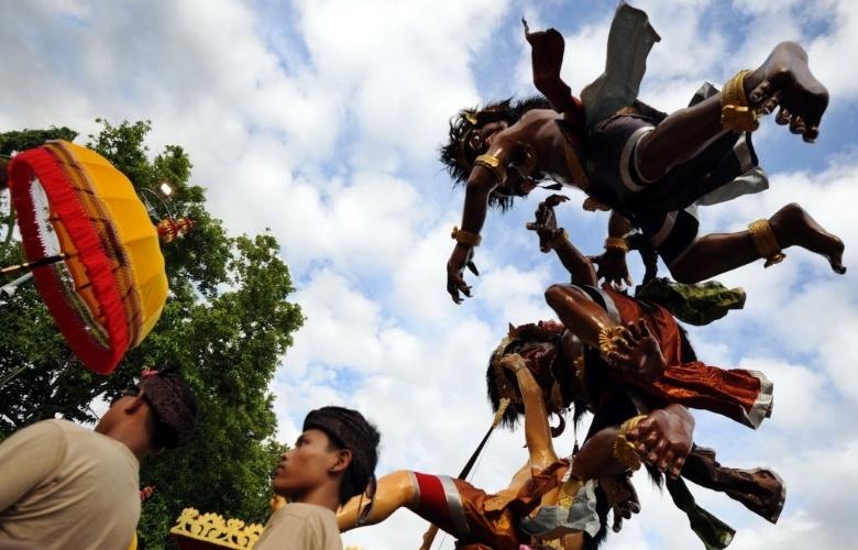 """11.mar.2013 - Hindus carregam imagens religiosas durante parada na véspera do Nyepi, o """"dia do silêncio"""" que marca o ano novo hindu, em Bali, na Indonésia"""