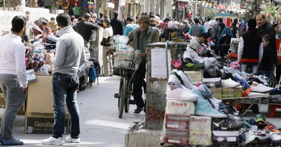 11.mar.2013 - Homem (centro) anda de bicicleta em área onde ambulantes vendem sapatos em Damasco, capital da Síria