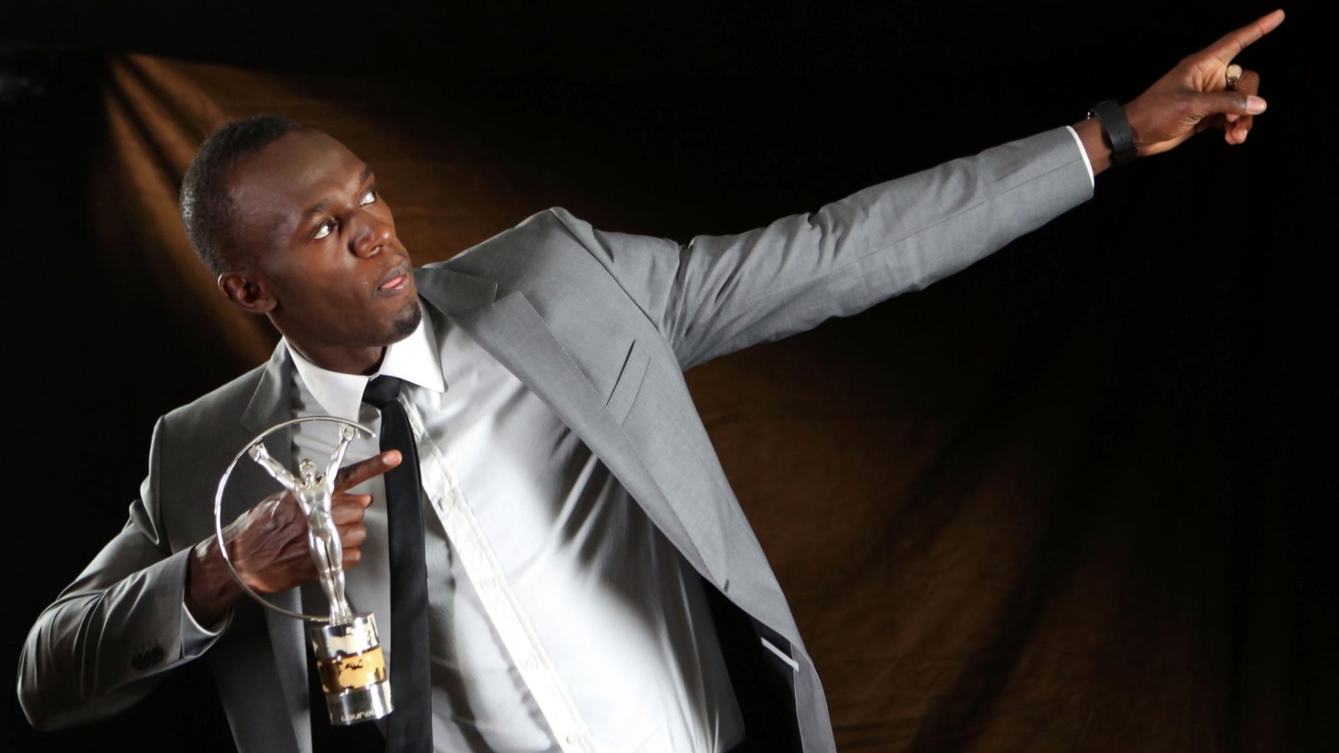 11.mar.2013 - O jamaicano Usain Bolt exibe o troféu conquistado como Melhor Atleta do Ano no Prêmio Laureus