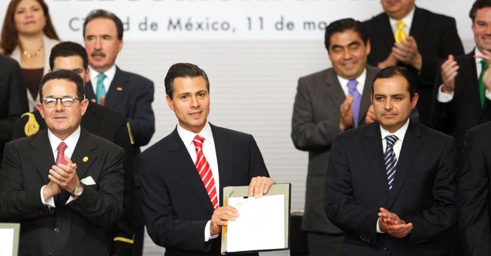 11.mar.2013 - O presidente do México, Henrique Peña Nieto (no centro), mostra o projeto de reforma constitucional, apresentado nesta segunda-feira (11) pelo governo mexicano, que busca acabar com os monopólios no setor de telecomunicações e que favorece a concorrência na televisão, na telefonia e na internet de banda larga