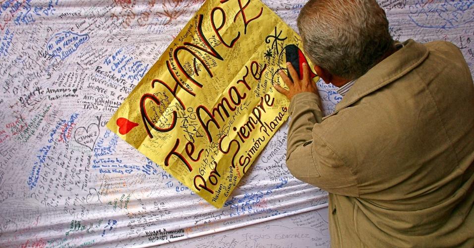 11.mar.2013 - Partidário do presidente venezuelano, Hugo Chávez, assinam cartazes com frases de apoio na Academia Militar, em Caracas, onde o corpo de Chávez está sendo velado