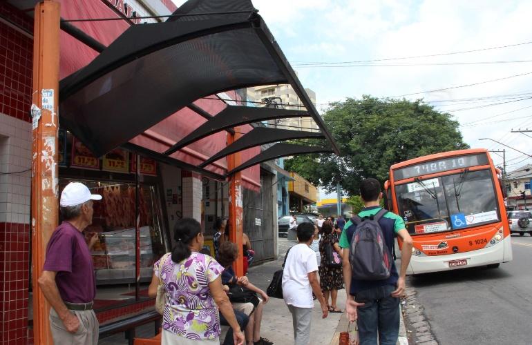 11.mar.2013 - Passageiros esperam ônibus em abrigo destruído na avenida Rio Pequeno, zona oeste de São Paulo