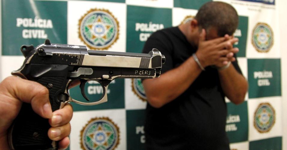 11.mar.2013 - Policial mostra pistola falsa utilizada por Bruno Antônio Dias Lima (à dir.), 37. Ele foi preso na madrugada deste domingo (10), em uma casa de shows na zona oeste do Rio de Janeiro, acusado de se passar por policial civil. Além da pistola falsa, foram apreendidos com ele um revólver calibre 38, algemas, um distintivo e uma carteira de policial civil falsificada