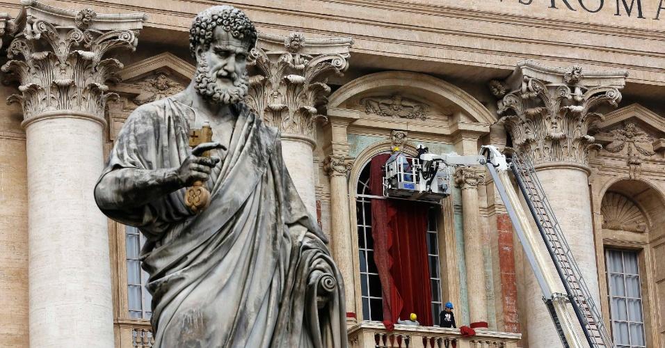 11.mar.2013 - Trabalhador coloca cortina vermelha na sacada central da Basílica de São Pedro, no Vaticano. É naquele local que o novo papa, eleito no conclave, fará sua primeira aparição