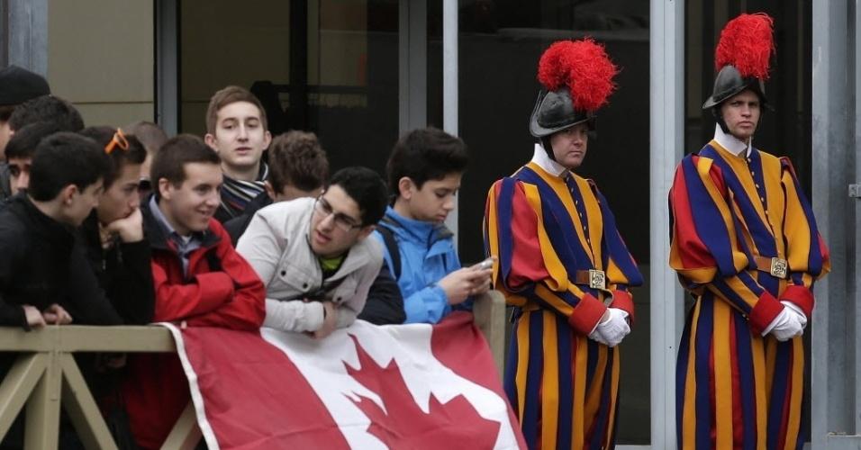11.mar.2013 - Vigiados por guardas suíços (direita), jovens do Canadá acompanham movimentação de cardeais às vésperas do conclave para escolher o novo papa, na praça de São  Pedro, no Vaticano