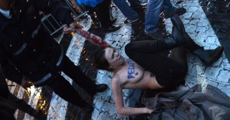 12.mar.2013 - Ativista do coletivo feminista Femen é detida por policiais próximo da praça São Pedro, no Vaticano, durante protesto contra o conclave. As jovens escreveram em seus corpos