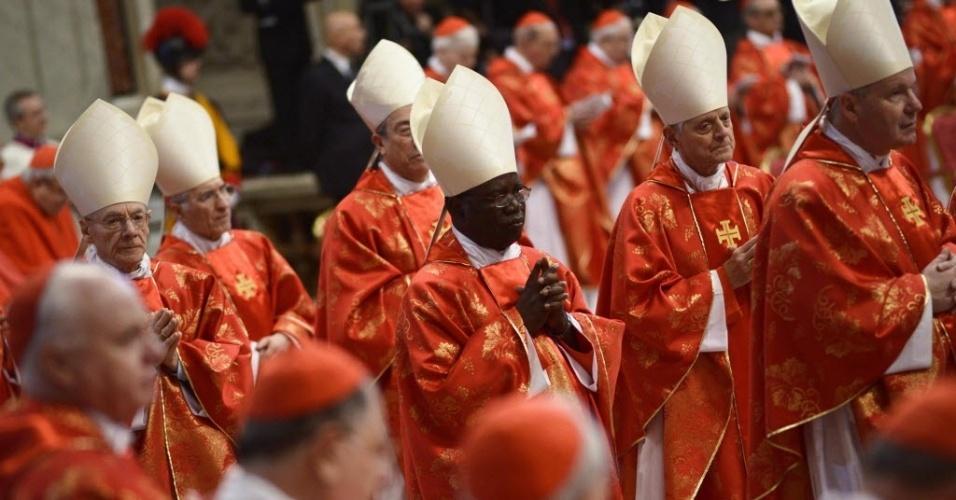 12.mar.2013 - Cardeais se levantam para orar durante a missa