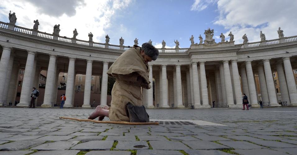 12.mar.2013 - Fiel reza na praça de São Pedro, em frente à basílica de mesmo nome, onde é celebrada a missa que marca o início do conclave que vai eleger o novo para