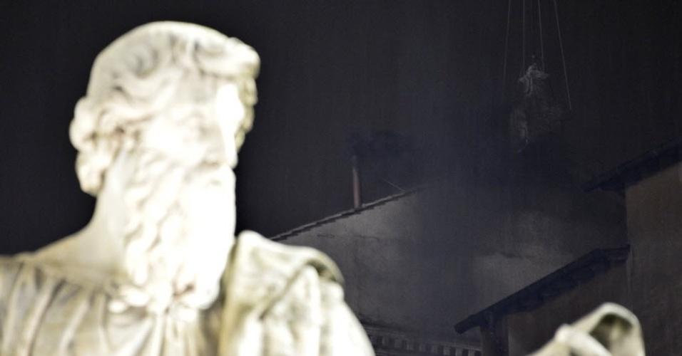 12.mar.2013 - Fumaça preta que sai do topo da Capela Sistina (fundo) é vista da Praça São Pedro, no Vaticano, nesta terça-feira. A cor da fumaça indica que os 115 cardeais não chegaram a um consenso sobre a escolha do novo papa no primeiro dia do conclave