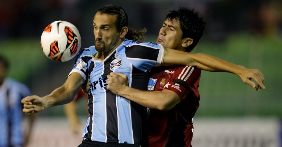 12.mar.2013 - Hernán Barcos, atacante do Grêmio, disputa a bola com Andres Sanchez, do Caracas