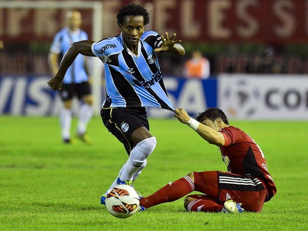 12.mar.2013 - Meia Zé Roberto, do Grêmio, é puxado pela camisa por Juan Guerra, do Caracas (VEN)