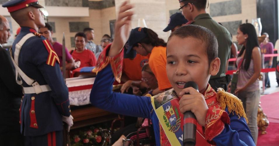 12.mar.2013 - Menino fantasiado de Simón Bolivar canta próximo ao caixão com o corpo do ex-presidente venezuelano Hugo Chávez, na Academia Militar em Caracas, onde milhares de pessoas continuam fazendo filas para se despedir do líder. Chávez morreu vítima de um câncer em 5 de março