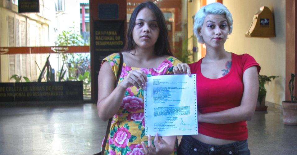 12.mar.2013 - Sara Winter (direita) e Anna Steel, Integrantes do braço brasileiro do grupo feminista Femen, exibem boletim de ocorrência na entrada do Cartório do 4º Juizado Especial Criminal, no Leblon, no Rio de Janeiro (RJ)