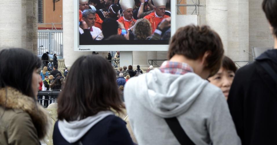 12.mar.2013 - Turistas acompanham da praça de São Pedro, no Vaticano, a missa que marca o início do conclave que vai eleger o novo para