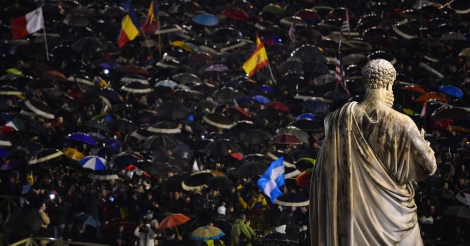 13.mar.2013 - Pessoas que lotam a praça São Pedro, no Vaticano, comemoram após fumaça branca ser expelida da chaminé da Capela Sistina, um sinal de que os cardeais reúnidos em Conclave escolheram o novo papa nesta quarta-feira (13)