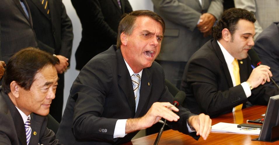 13.mar.2013 - Durante reunião da Comissão de Direitos Humanos da Câmara, o deputado Jair Bolsonaro (PP-RJ) discute com manifestantes contrários à eleição do pastor e deputado Marco Feliciano (PSC-SP) para a presidência da comissão. Nesta quarta-feira (13), Feliciano enfrentou protestos durante a primeira reunião comandada por ele e foi defendido por Bolsonaro, que reagiu aos protestos