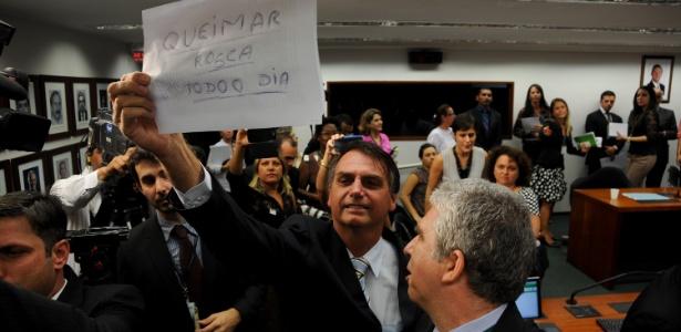 """Durante sessão da Comissão de Direitos Humanos da Câmara, o deputado Jair Bolsonaro (PP-RJ) mostra cartaz a manifestantes onde está escrito """"Queimar rosca todo o dia"""""""