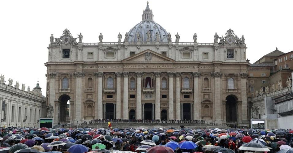 13.mar.2013 - Fiéis esperam debaixo de chuva o anúncio do resultado do segundo dia do conclave na praça São Pedro, no Vaticano
