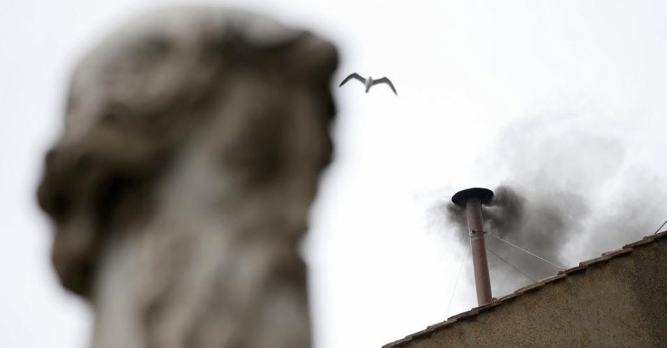 13.mar.2013 - Gaivota sobrevoa a Capela Sistina, no Vaticano, enquanto a fumaça preta anuncia que os cardeais enclausurados não definiram o nome do novo papa no segundo dia do conclave