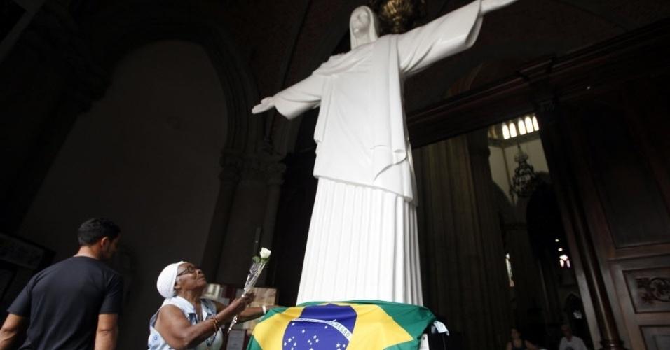 13.mar.2013 - Mulher estende a bandeira do Brasil aos pés de uma estátua de Cristo dentro da Igreja da Sé, em São Paulo. Cardeais enclausurados na Capela Sistina, no Vaticano, ainda não definiram o nome do sucessor do papa emérito Bento 16