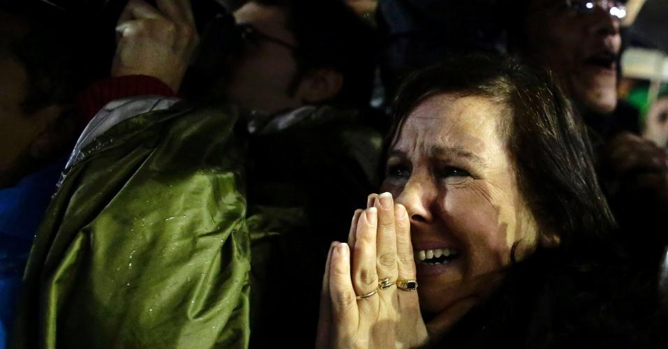 13.mar.2013 - Mulher se emociona ao observar a fumaça branca  que saiu da chaminé da Capela Sistina, no Vaticano,  o que indica que o novo papa foi escolhido. Ela faz parte da multidão de pessoas que aguarda a nomeação do novo pontífice na praça São Pedro, no Vaticano