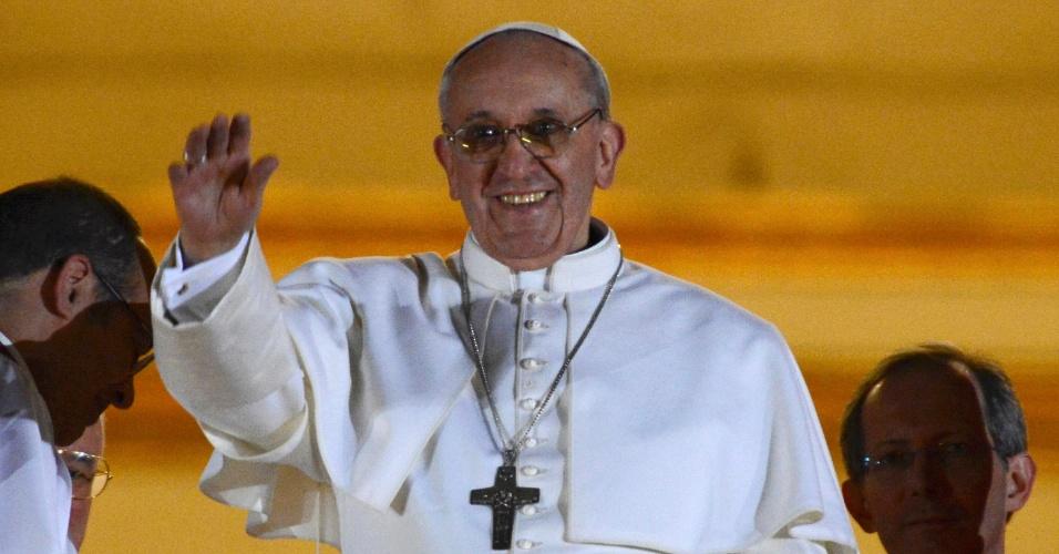 13.mar.2013 - O cardeal argentino Jorge Mario Bergoglio, nomeado papa Francisco 1º, sorri da sacada da basílica de São Pedro, no Vaticano, para a multidão de fiéis que se aglomeram na praça São Pedro