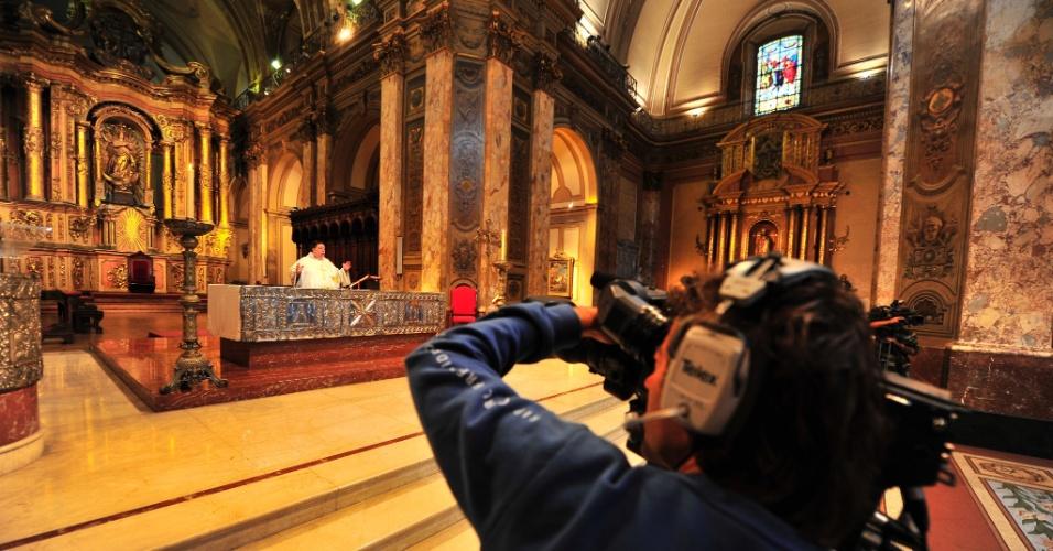14.mar.2013 - Cinegrafista grava missa de Alejandro Russo, pároco-chefe da catedral de Buenos Aires, na Argentina, nesta quinta-feira (14). A movimentação e o barulho da cobertura da imprensa mundial dentro da igreja onde o papa Francisco atuava até dias atrás acabou atrapalhando a missa