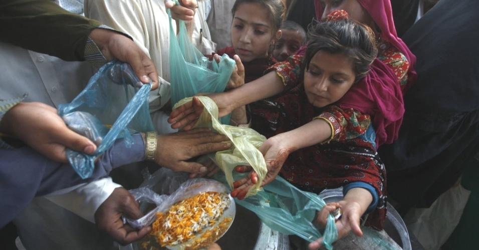 14.mar.2013 - Crianças seguram sacolas plásticas para receber doações de alimentos, no mausoléu Abdullah Shah Ghazi, em Karachi, no Paquistão
