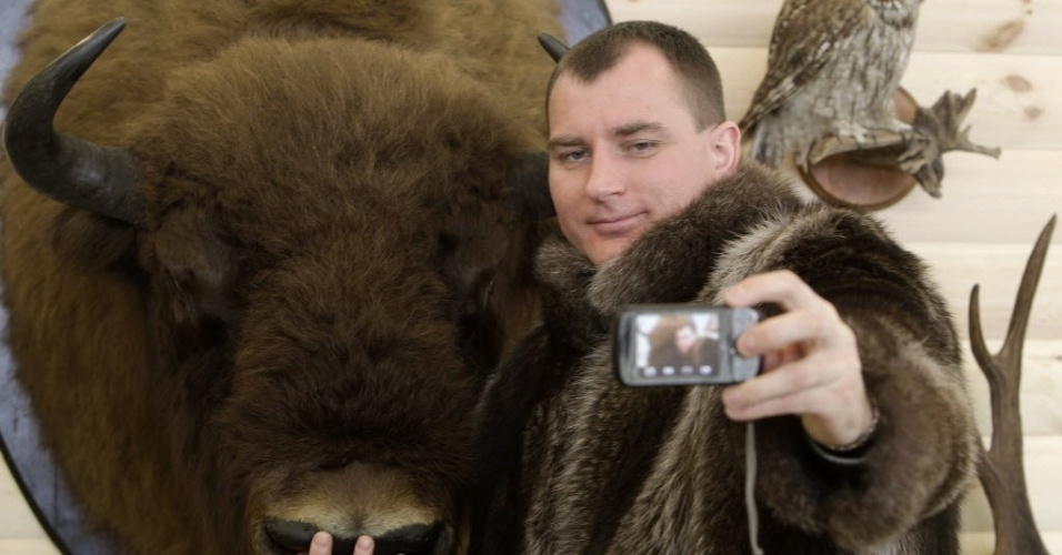 14.mar.2013 - Homem com jaqueta de guaxinim fotografa a si mesmo ao lado de bisão empalhado, durante feira internacional de caça e pesca em Minsk, capital de Belarus