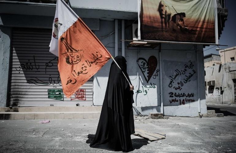 14.mar.2013 - Mulher segura bandeira do Bahrein com slogans contra o governo do país, no vilarejo de Jidhafs, a oeste de Manama, capital bahreinita